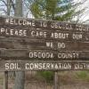 Before: The well-weathered Conservation District sign located on M-72 west of McCollum Lake greeted folks entering Oscoda County.